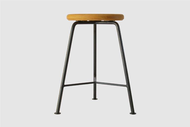 座面が木製で、3本の脚が鉄製のスツール