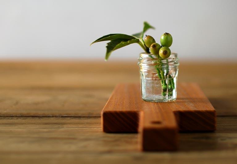 カッティングボードの上に、花を挿したガラス瓶