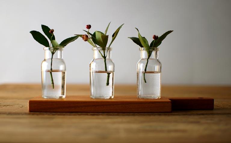 カッティングボードの上に、木の枝を挿したガラス瓶が3本