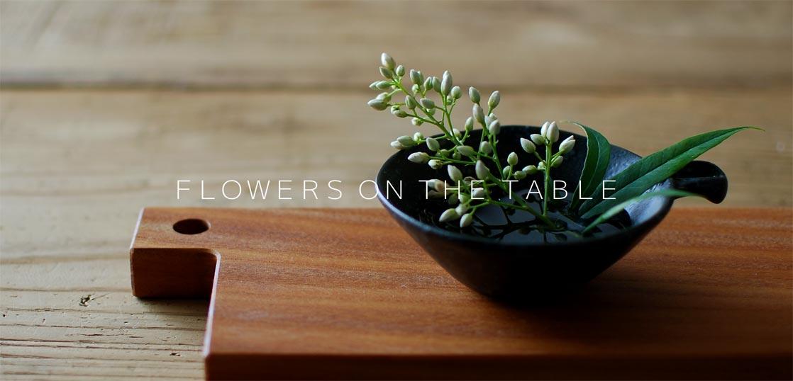 カッティングボードの上に、花を活けた豆皿