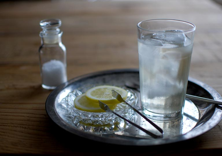 ジュースをグラスに注いだ様子、レモンと塩を添えて