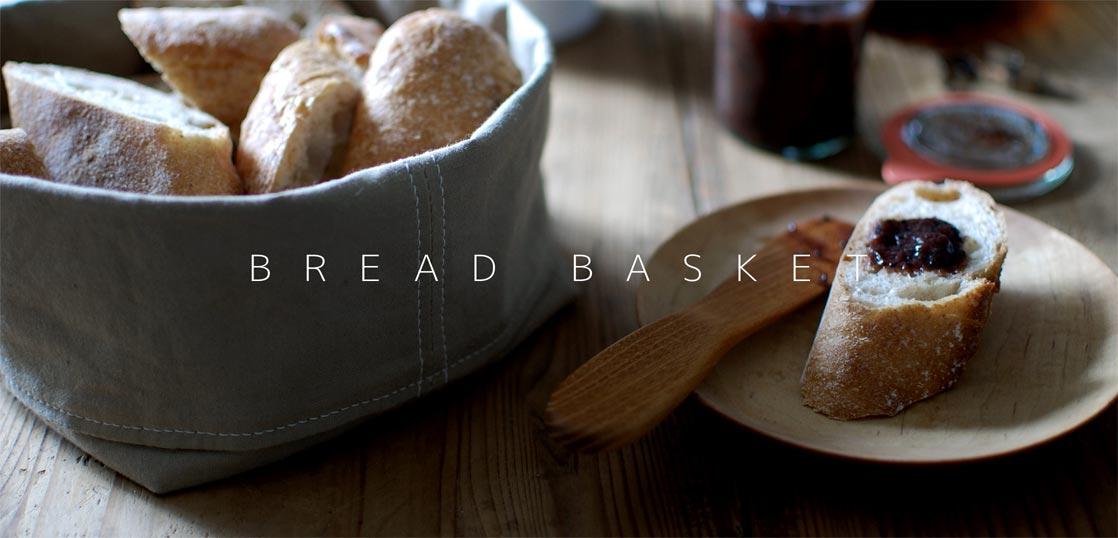 パンの入っているブレッドバスケットとバターナイフと木皿