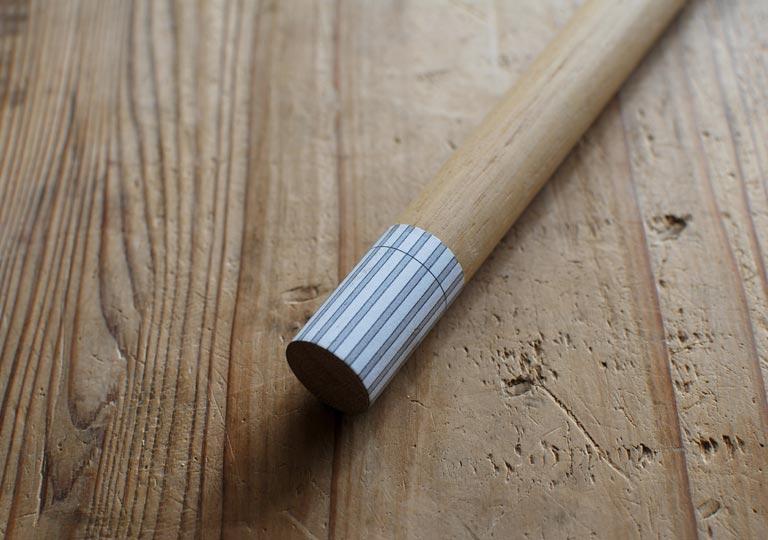 木の丸棒の先に作図した紙を貼る