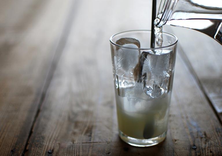 氷と原液を入れたグラスに水を注ぐ