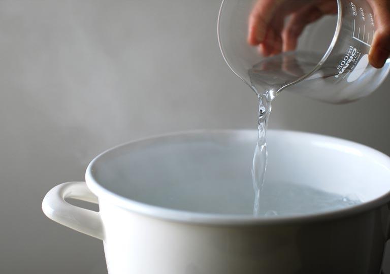 沸騰したお湯に水を入れている様子